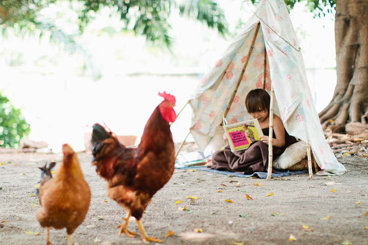 top five summer reads, summer reading, boy reading in a tent, reading in a tee-pee, reading in a tent, reading outside with chickens, reading outside in africa, reading outside